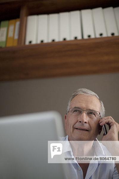 Älterer Mann beim Telefonieren am Schreibtisch