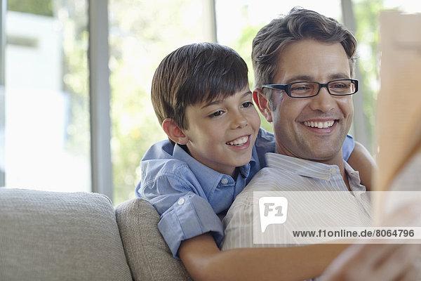 Vater und Sohn umarmen sich auf dem Sofa
