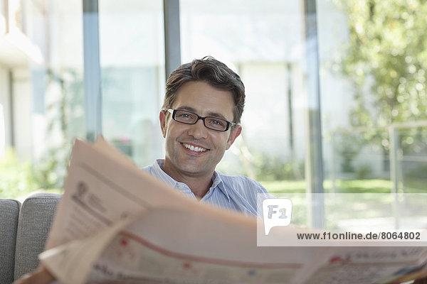 Geschäftsmann beim Zeitungslesen auf dem Sofa