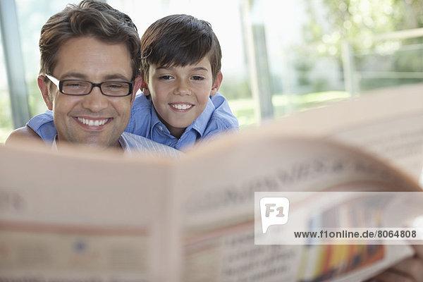 Vater und Sohn lesen gemeinsam Zeitung