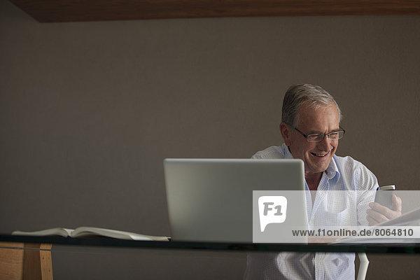 Geschäftsmann mit Handy am Schreibtisch