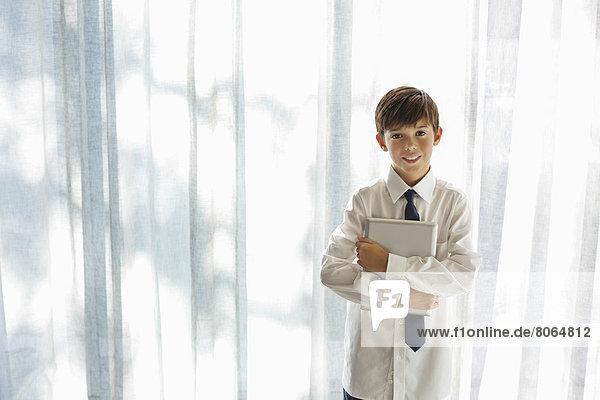 Junge in Hemd und Krawatte mit Tablet-Computer
