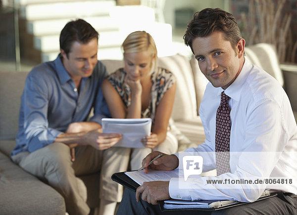 Finanzberater mit Paar auf Sofa