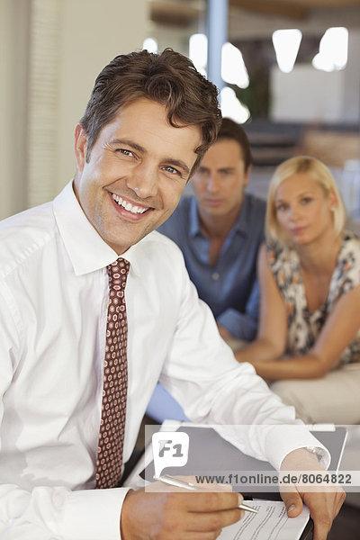 Finanzberater lächelt mit Paar auf Sofa