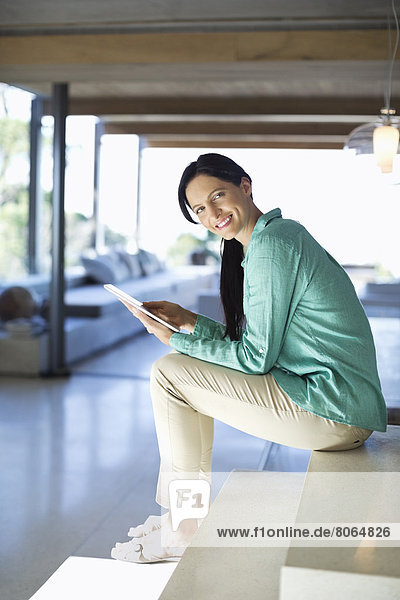 Frau mit Tablet-Computer auf Stufen