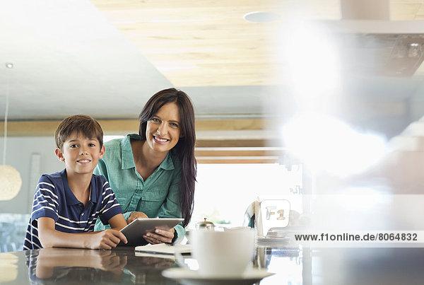 Mutter und Sohn mit Tablet-Computer in der Küche