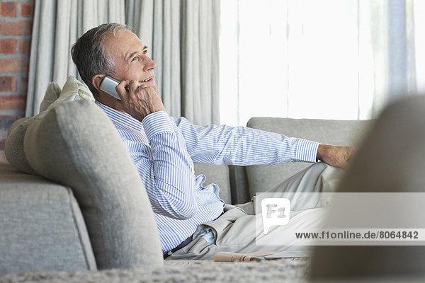 Älterer Mann beim Telefonieren auf dem Sofa