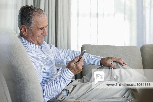 Älterer Mann mit Handy auf dem Sofa