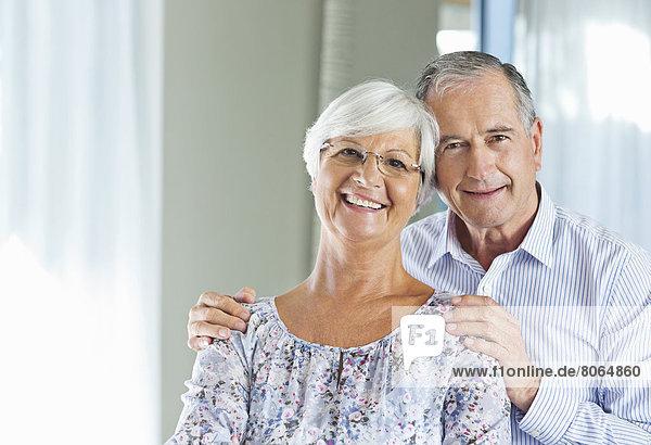 Älteres Paar lächelt zusammen im Haus