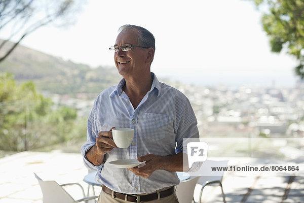 Mann trinkt eine Tasse Kaffee im Freien