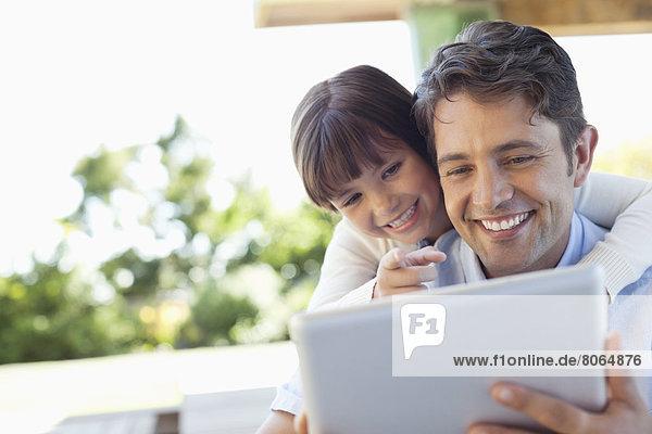 Vater und Tochter nutzen gemeinsam den Tablet-Computer