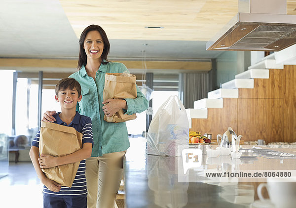 Mutter und Sohn mit Lebensmitteln in der Küche