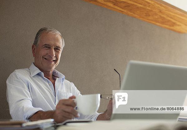 Älterer Mann bei einer Tasse Kaffee am Schreibtisch