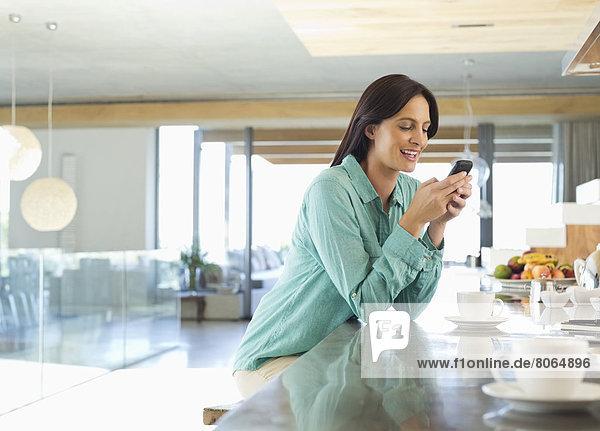 Frau mit Handy in der Küche