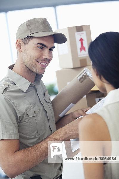 Lieferjunge mit Paketen für Geschäftsfrau