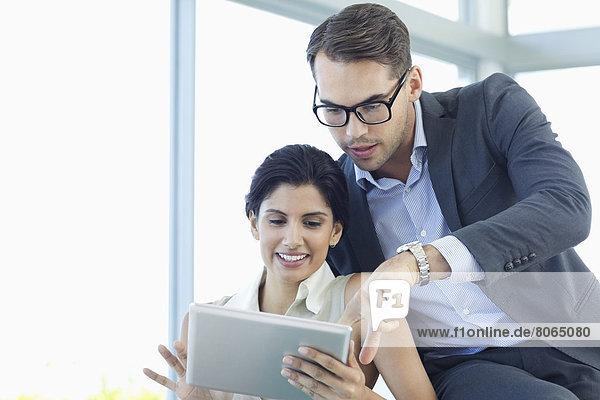 Geschäftsleute mit Tablet-Computer auf dem Sofa