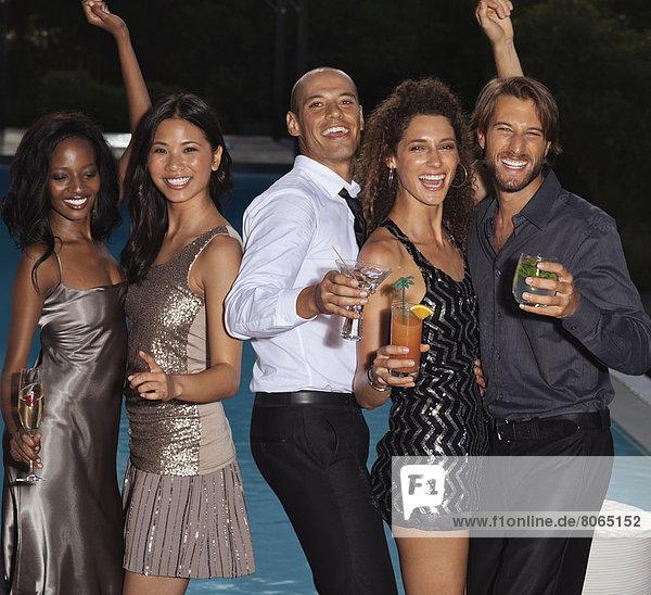 Freunde tanzen auf der Party am Swimmingpool