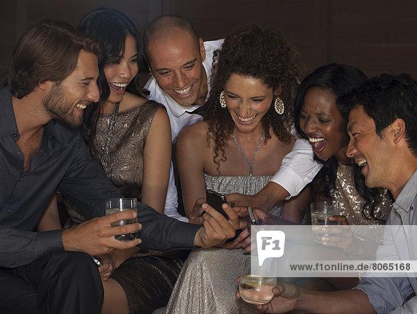 Freunde  die auf der Party mit dem Handy telefonieren