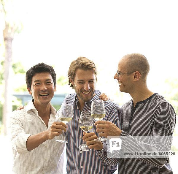 Männer stoßen sich gegenseitig mit Wein an.