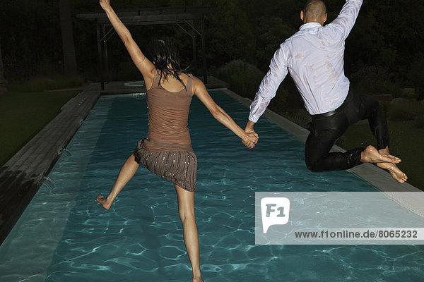 Voll gekleidete Freunde beim Sprung ins Schwimmbad