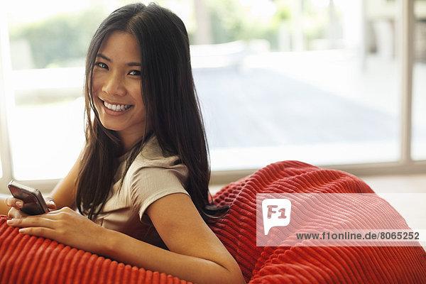 Frau mit Handy im Sitzsackstuhl