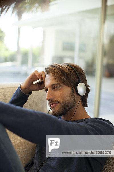 Mann hört Kopfhörer auf dem Sofa