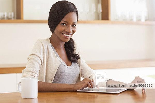 Frau mit Tablet-Computer am Tisch