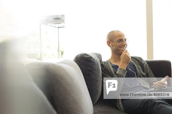Mann spricht auf dem Kopfhörer auf dem Sofa