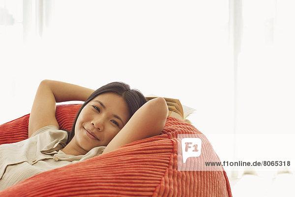 Lächelnde Frau entspannt im Sitzsackstuhl
