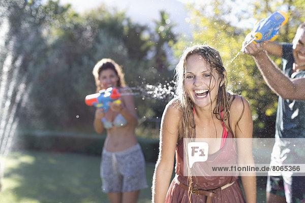 Freunde spielen mit Wasserpistolen im Hinterhof