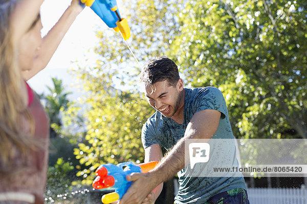 Pärchen spielen mit Wasserpistolen im Garten
