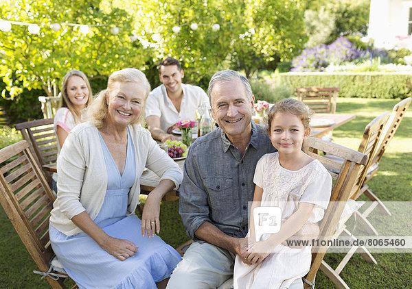 Familie lächelt bei Tisch im Freien