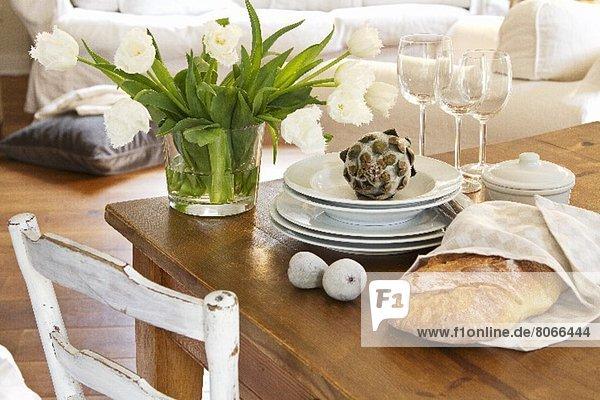 Weisser Tulpenstrauss in Glasvase neben Tellerstapel  Weingläsern  Dekofeigen und Deko-Artischocke