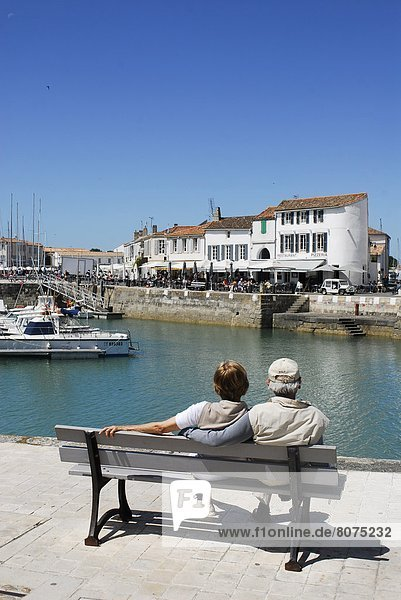 'Tourists on the quays of the harbour of Saint-Martin de Ré on the Isle of Rhé (''Ile de Ré'' in French) (17). Couple of retired people seated on a bench viewed from behind'