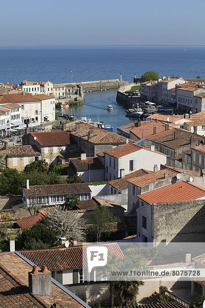 'View of the red tiled roofs of Saint-Martin-en-Re  ''ile de Re''  Isle of Rhe  along the Atlantic coast in the Charente-Maritime department (17). The town  the far end of the harbour and view of the sea. (All rights reserved. Only postcard production).'