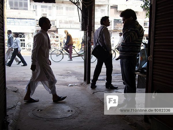 Silhouette of men walking on path amid closed shops in New Delhi  India.