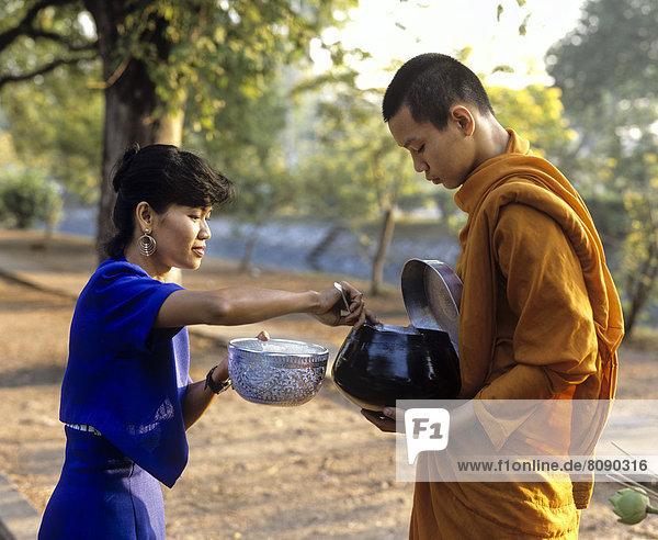 Mönch beim Bettelgang  Frau gibt einem buddhistischen Mönch Reis in die Bettelschale