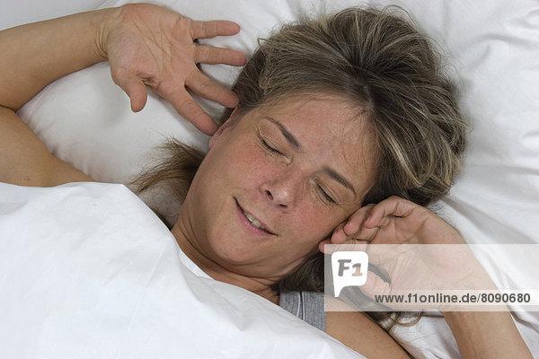 Frau im Bett  wacht auf