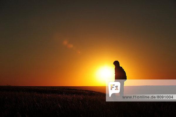 Frau wandert im Sonnenuntergang durch die Prärie