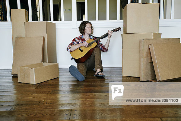 Caucasian man playing guitar in new home