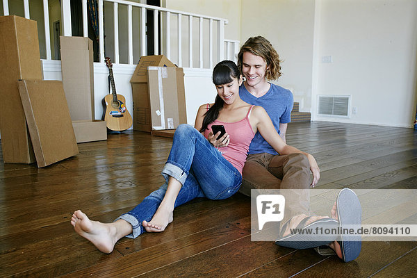 Couple using cell phone in new home