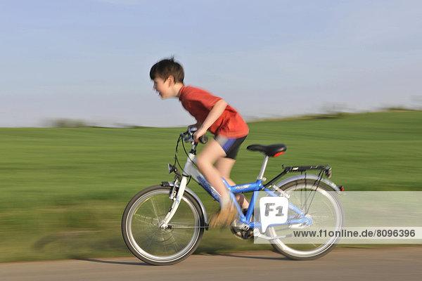 Junge fährt Fahrrad auf asphaltiertem Feldweg