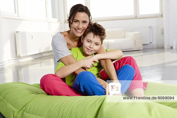Mutter und Sohn in Freizeitkleidung sitzt auf Sitzsack in einem Loft