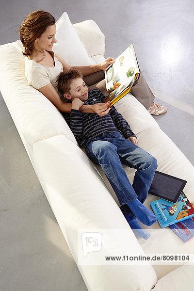 Mutter und Sohn mit Buch auf Sofa