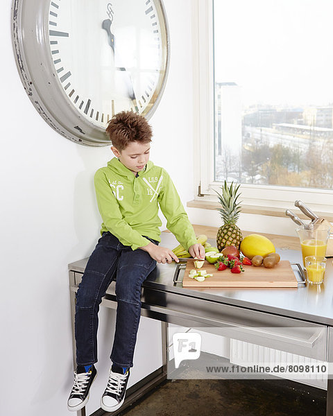 Junge sitzt auf Küchenarbeitsplatte und schneidet verschiedene Sorten Obst auf Schneidebrett