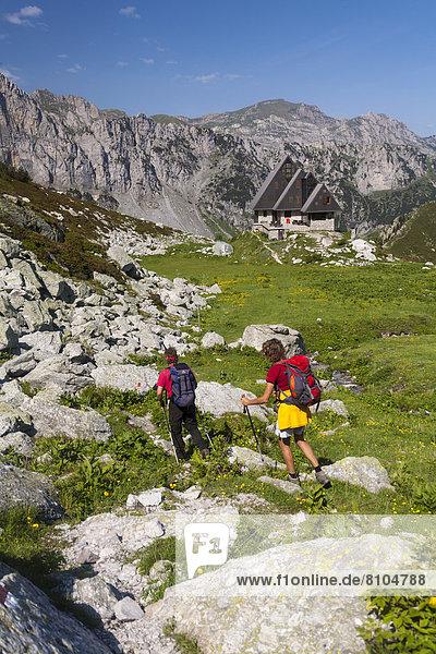 Zwei Wanderer  hinten die Berghütte Rifugio Garelli