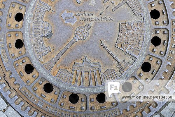 Diverse Berliner Wahrzeichen wie Brandenburger Tor  Fernsehturm  Reichstag  Siegessäule auf Gullideckel  Kanaldeckel der Berliner Wasserbetriebe