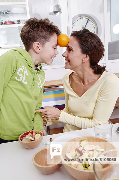 Mother and son playing at home with an orange