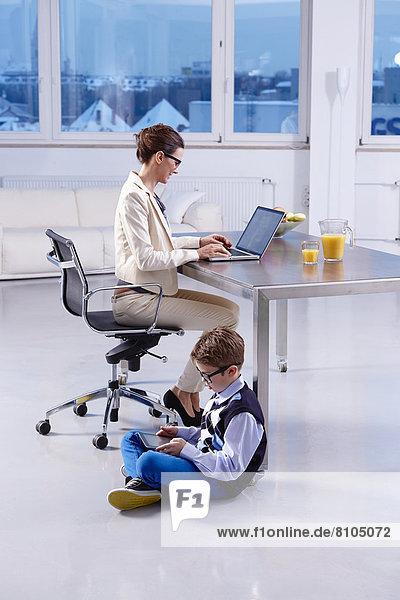 Junge sitzt mit einem Tablet-PC auf dem Boden  Mutter sitzt am Schreibtisch und arbeitet am Laptop