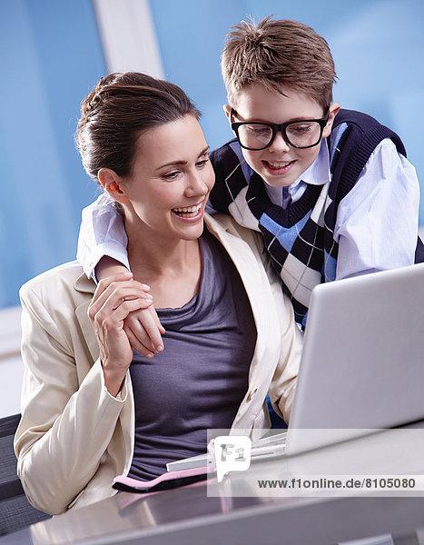 Junge mit Brille legt den Arm um seine Mutter  beide schauen auf einen Laptop